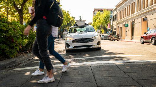 Ein autonomes Auto mit Radar-Aufbau fährt auf einen Fußgängerüberweg zu